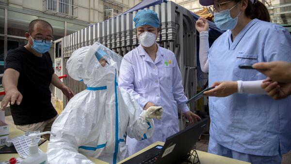 Chińscy pracownicy służby zdrowia wykonujący testy na koronawirusa - Sputnik Polska