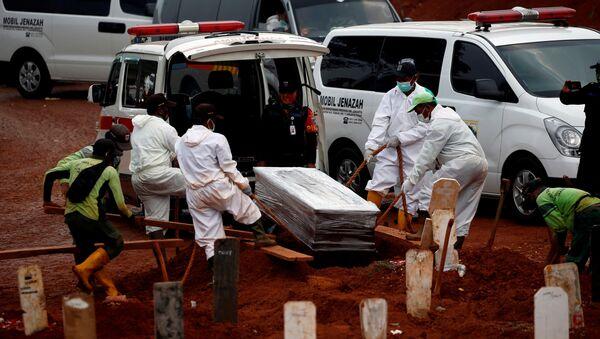 Pogrzeb ofiar COVID-19 na cmentarzu w Dżakarcie - Sputnik Polska