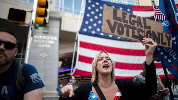 """Zwolenniczka Donalda Trumpa z plakatem """"Tylko legalne głosy"""" na ulicy w Filadelfii - Sputnik Polska"""