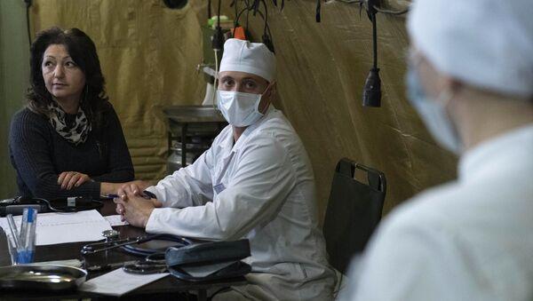 Lekarz przyjmuje pacjenta w szpitalu polowym rozmieszczonym przez rosyjskie Ministerstwo Obrony na lotnisku w Stepanakercie - Sputnik Polska
