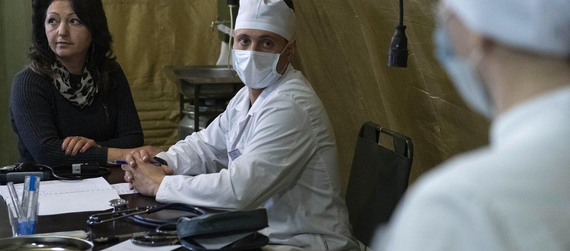 Lekarz przyjmuje pacjenta w szpitalu polowym rozmieszczonym przez rosyjskie Ministerstwo Obrony na lotnisku w Stepanakercie - Sputnik Polska, 1920, 20.02.2021