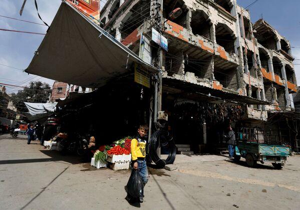 Chłopiec z reklamówką przed sklepem w syryjskim mieście Duma - Sputnik Polska