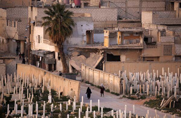 Ludzie przed cmentarzem w syryjskim mieście Duma - Sputnik Polska