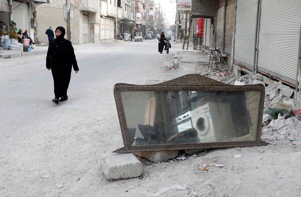 Kobieta przechodzi obok lustra na ulicy w syryjskim mieście Duma - Sputnik Polska