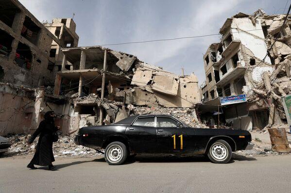 Kobieta przechodzi obok zniszczonego domu w Dumie, na przedmieściach Damaszku, Syria - Sputnik Polska