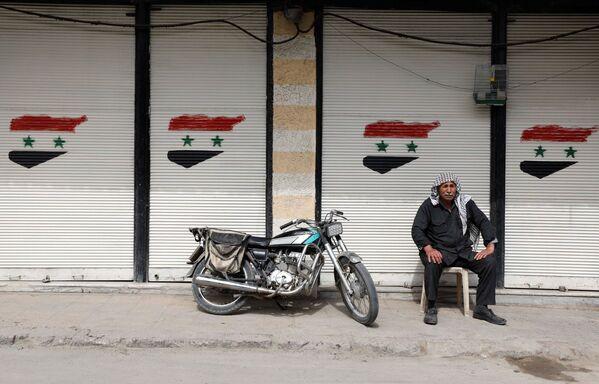 Mężczyzna siedzi przed zamkniętym sklepem w Dumie, na przedmieściach Damaszku, Syria - Sputnik Polska