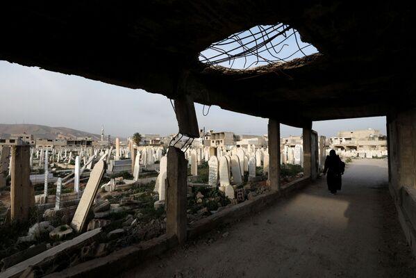 Kobieta idzie na cmentarzu w Dumie, na przedmieściach Damaszku, Syria - Sputnik Polska
