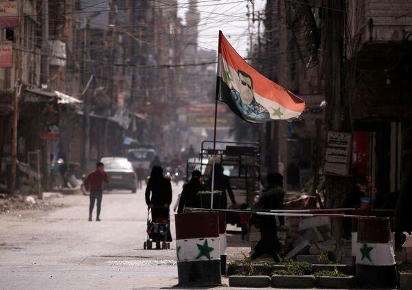 Flaga narodowa z wizerunkiem prezydenta Baszara al-Asada rozwiewa w punkcie kontrolnym w Dumie, na przedmieściach Damaszku, Syria - Sputnik Polska
