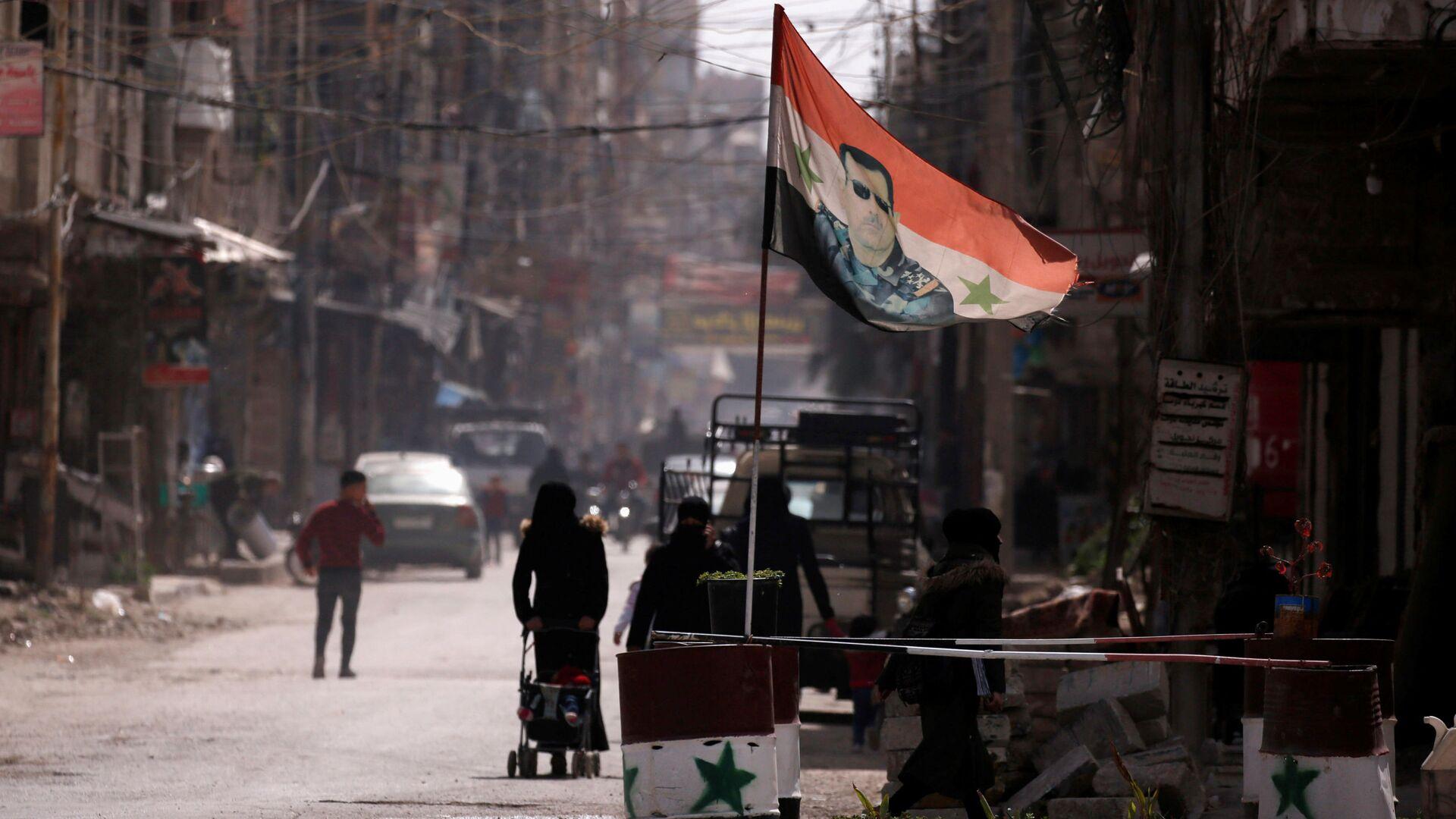 Flaga narodowa z wizerunkiem prezydenta Baszara al-Asada rozwiewa w punkcie kontrolnym w Dumie, na przedmieściach Damaszku, Syria - Sputnik Polska, 1920, 01.08.2021
