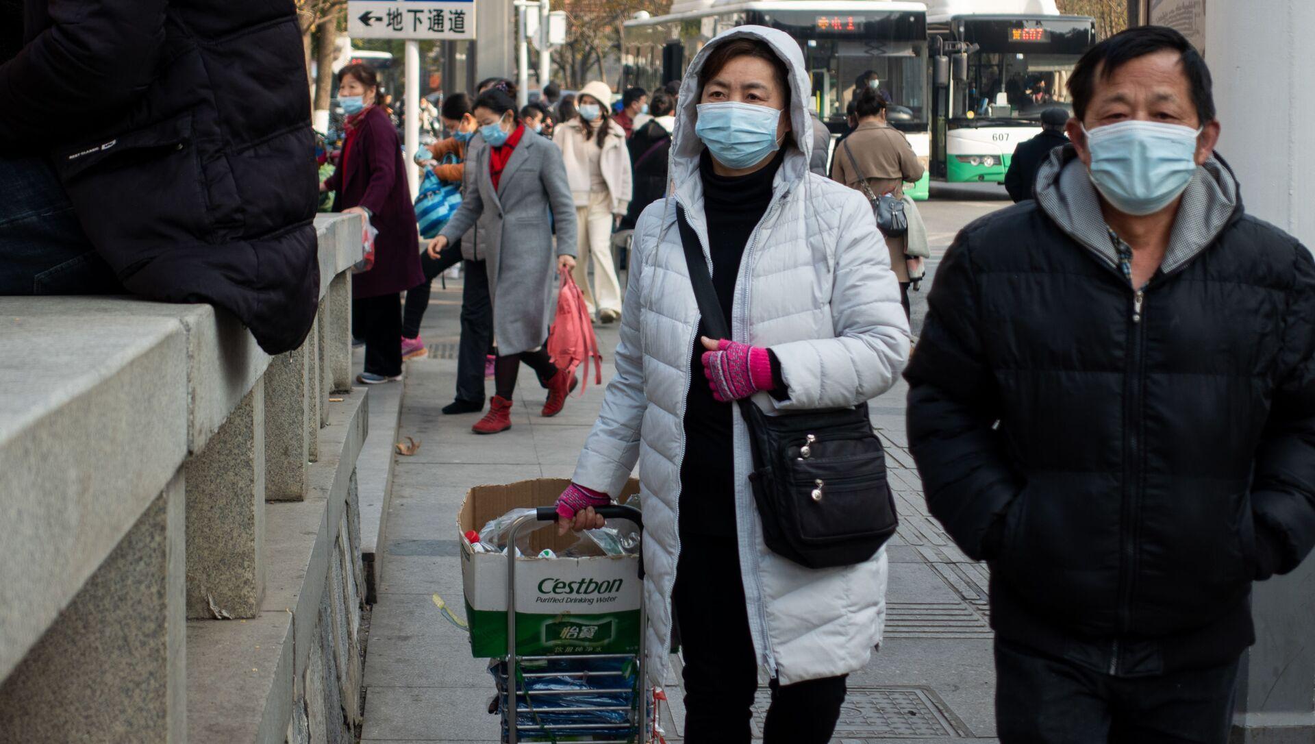 Ludzie w maskach ochronnych na ulicy w Wuhan w Chinach - Sputnik Polska, 1920, 29.03.2021
