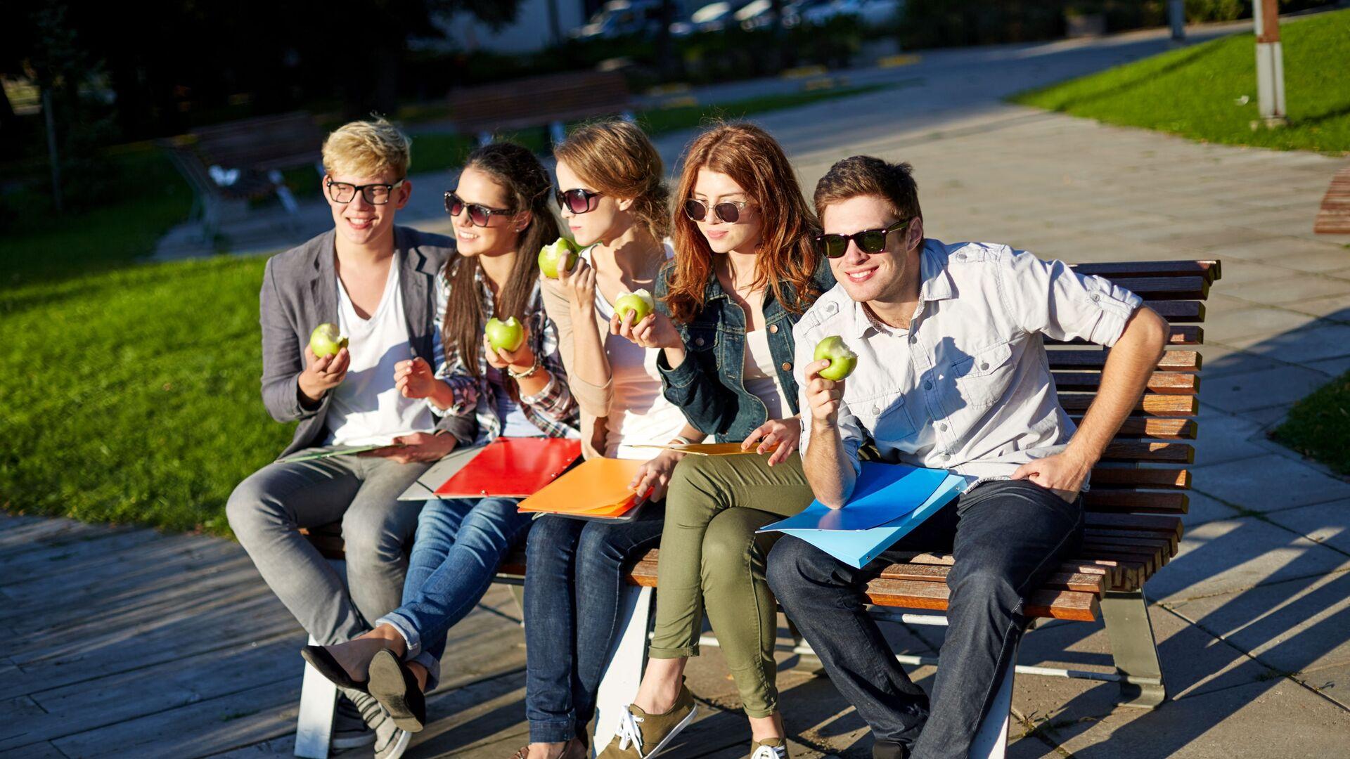 Młodzi ludzie jedzą jabłka na ławeczce w parku. - Sputnik Polska, 1920, 06.10.2021