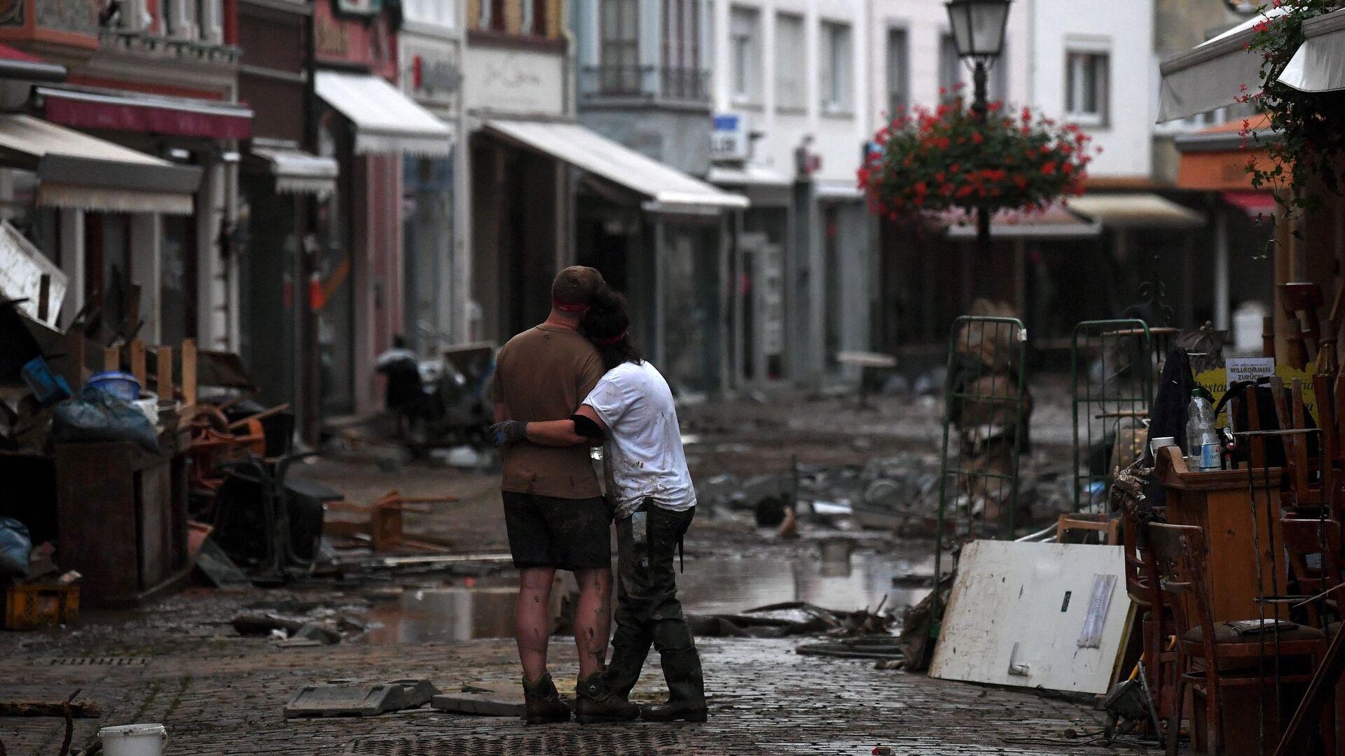 Пара обнимаются, стоя среди обломков, в городе Бад-Нойенар-Арвайлер, Германия  - Sputnik Polska, 1920, 26.07.2021
