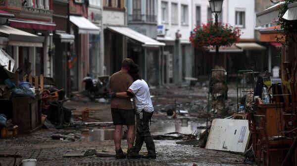 Пара обнимаются, стоя среди обломков, в городе Бад-Нойенар-Арвайлер, Германия  - Sputnik Polska