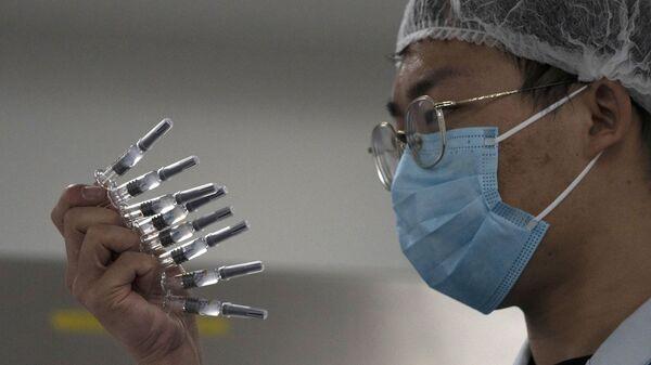 Сотрудник проверяет шприцы с вакциной против вируса SARS-CoV-2 на заводе в Пекине - Sputnik Polska