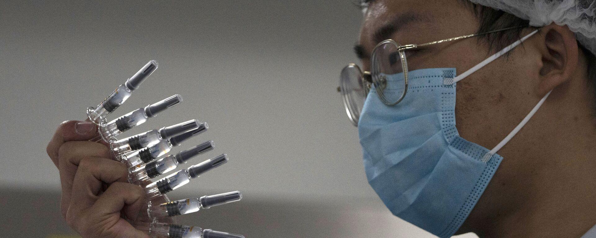 Pracownik kontroluje strzykawki zawierające szczepionkę przeciwko SARS-CoV-2 w fabryce w Pekinie - Sputnik Polska, 1920, 30.09.2021