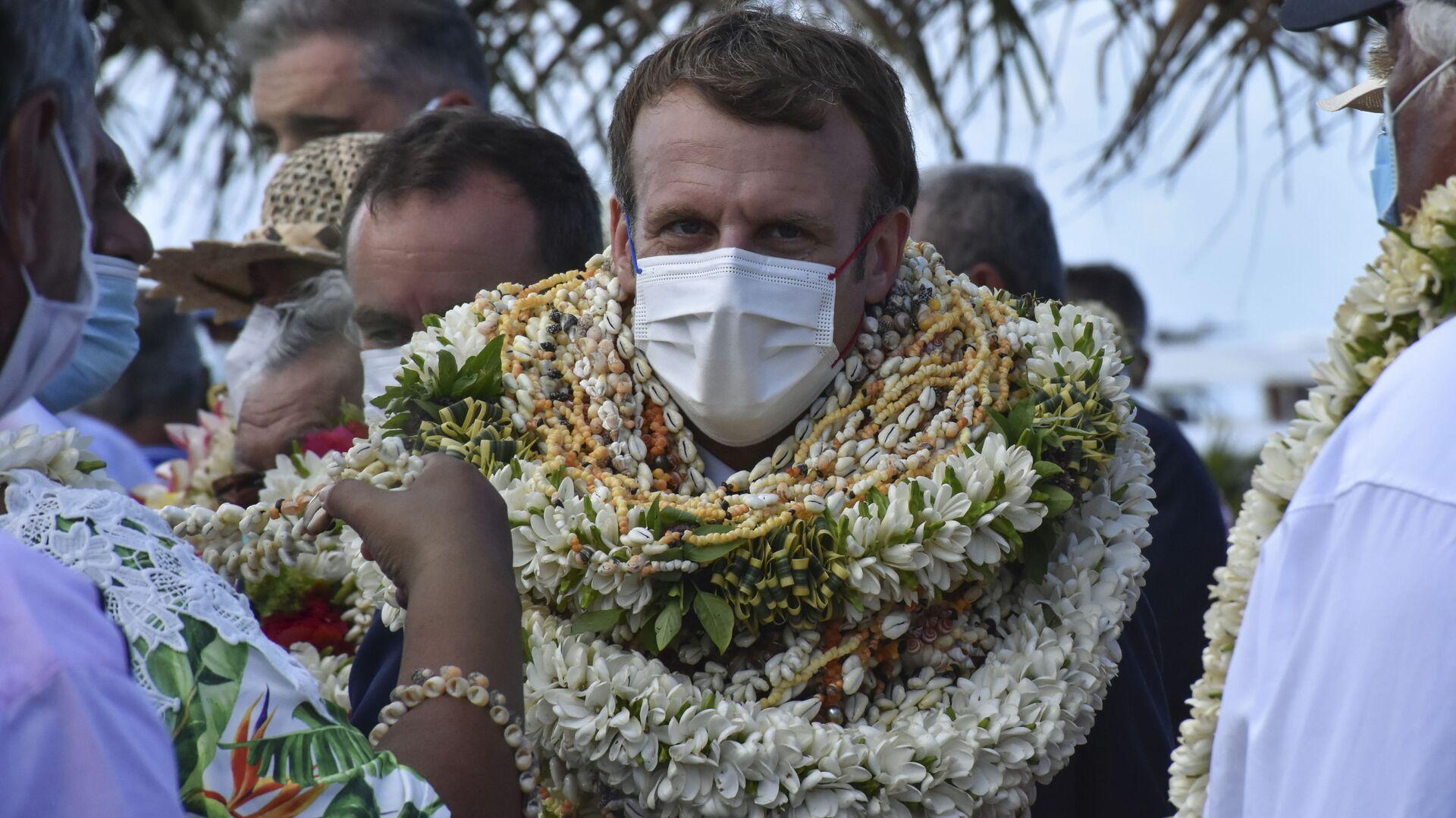 Prezydent Francji Emmanuel Macron w wiankach z kwiatów i naszyjnikach - Sputnik Polska, 1920, 28.07.2021