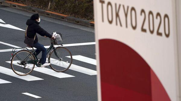 Велосипедист в защитной маске на фоне баннера Олимпиады 2020 в Токио - Sputnik Polska