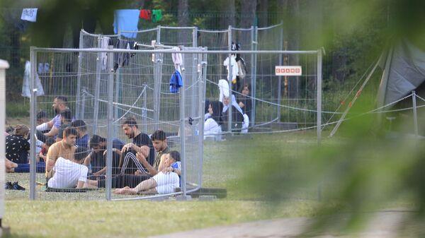 Через заборы видны мигранты, сидящие на земле в лагере недалеко от приграничного города Капчяместис, Литва - Sputnik Polska