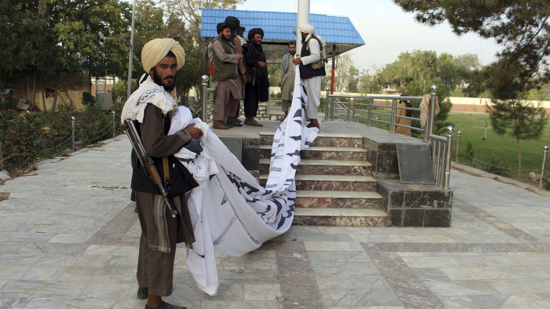 Bojownicy Taliban* wznoszą swoją flagę przed rezydencją gubernatora prowincji Ghazni, południowy wschód Afganistanu - Sputnik Polska, 1920, 09.10.2021