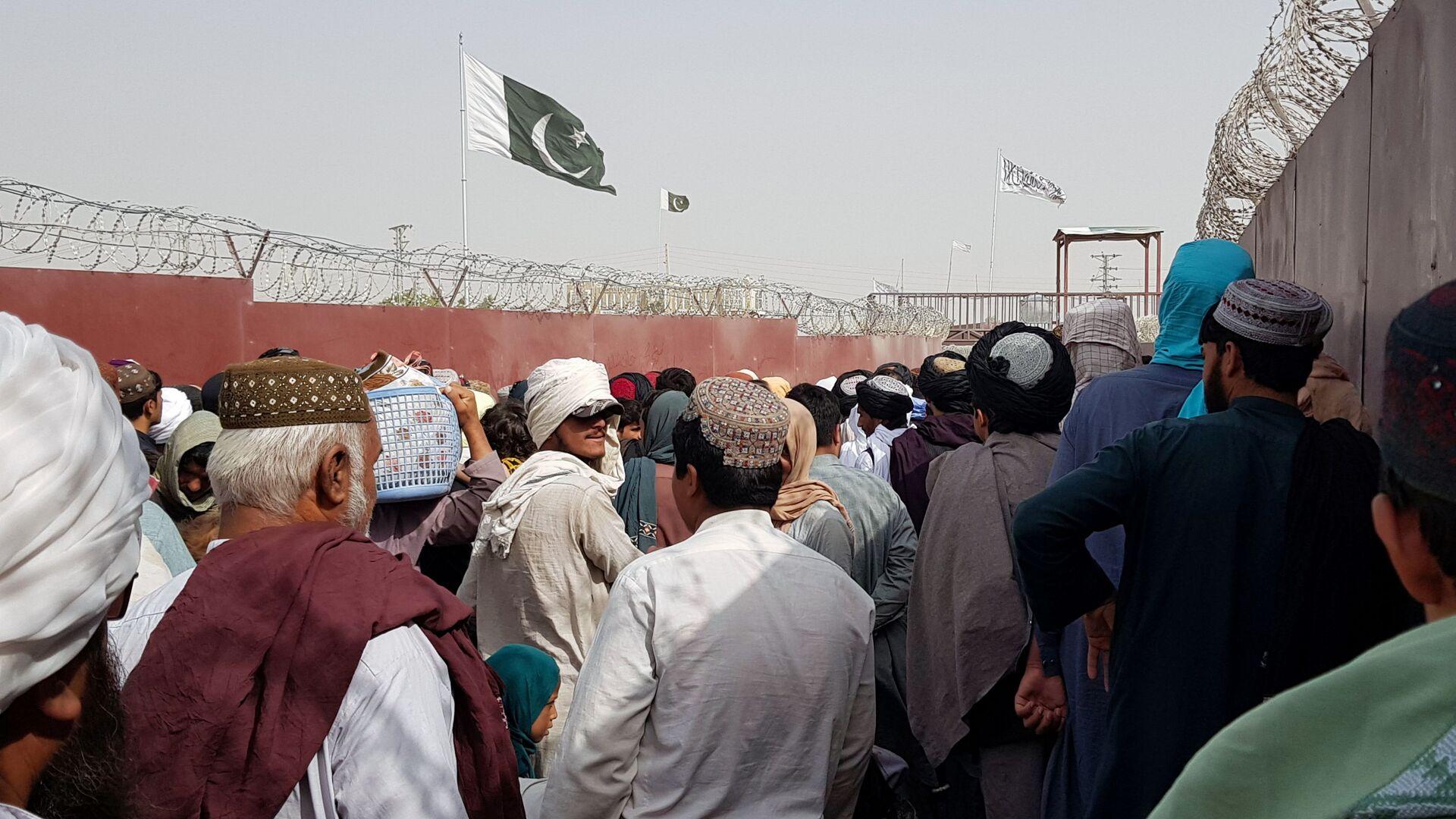Flaga Pakistanu i flaga talibów widoczne na tylnym planie, kiedy ludzie kierują się do Afganistanu na przejściu granicznym Brama Przyjaźni w pakistańsko-afgańskim mieście granicznym Ćaman, Pakistan 15 sierpnia 2021 roku. - Sputnik Polska, 1920, 17.08.2021