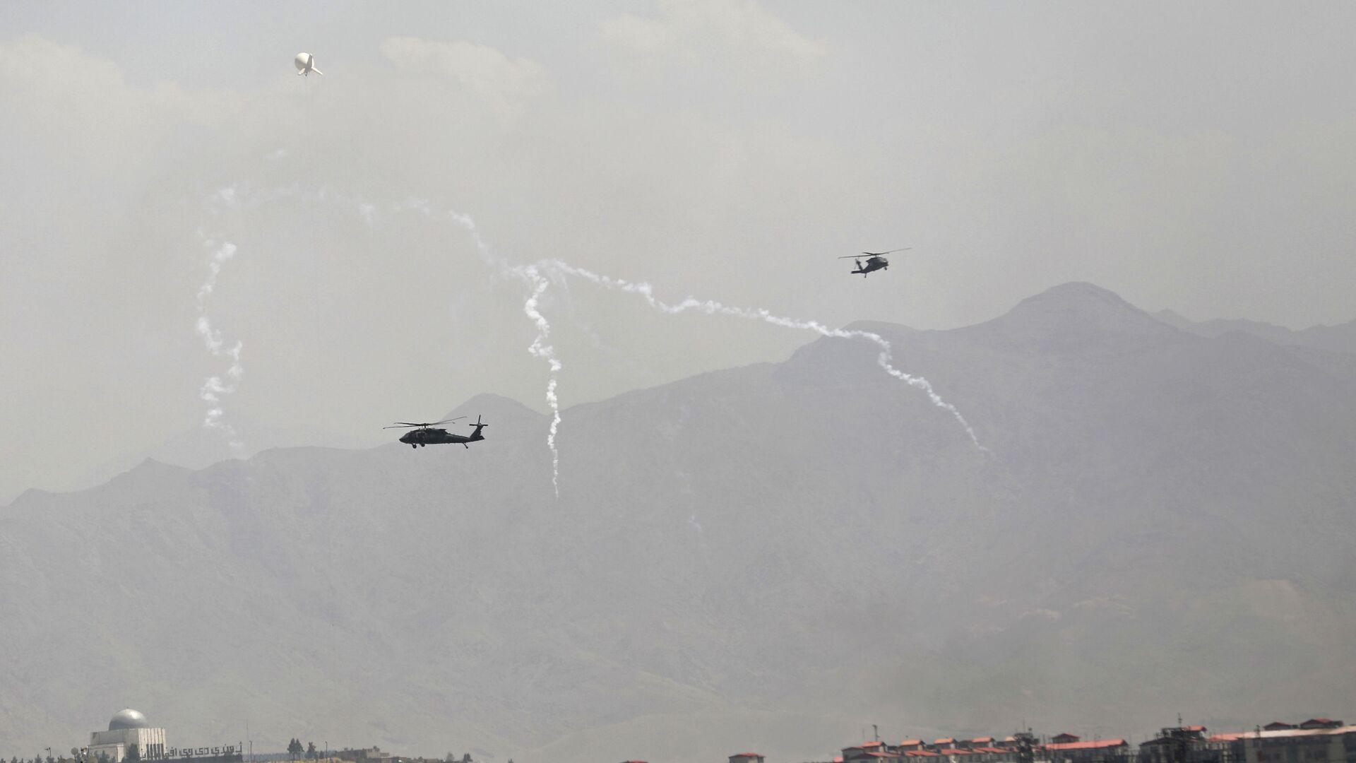 Wabiki przeciwrakietowe zostają uruchomione, gdy śmigłowce USA Black Hawk i balon sterowca przelatują nad miastem Kabul w Afganistanie, niedziela, 15 sierpnia 2021 roku - Sputnik Polska, 1920, 17.08.2021