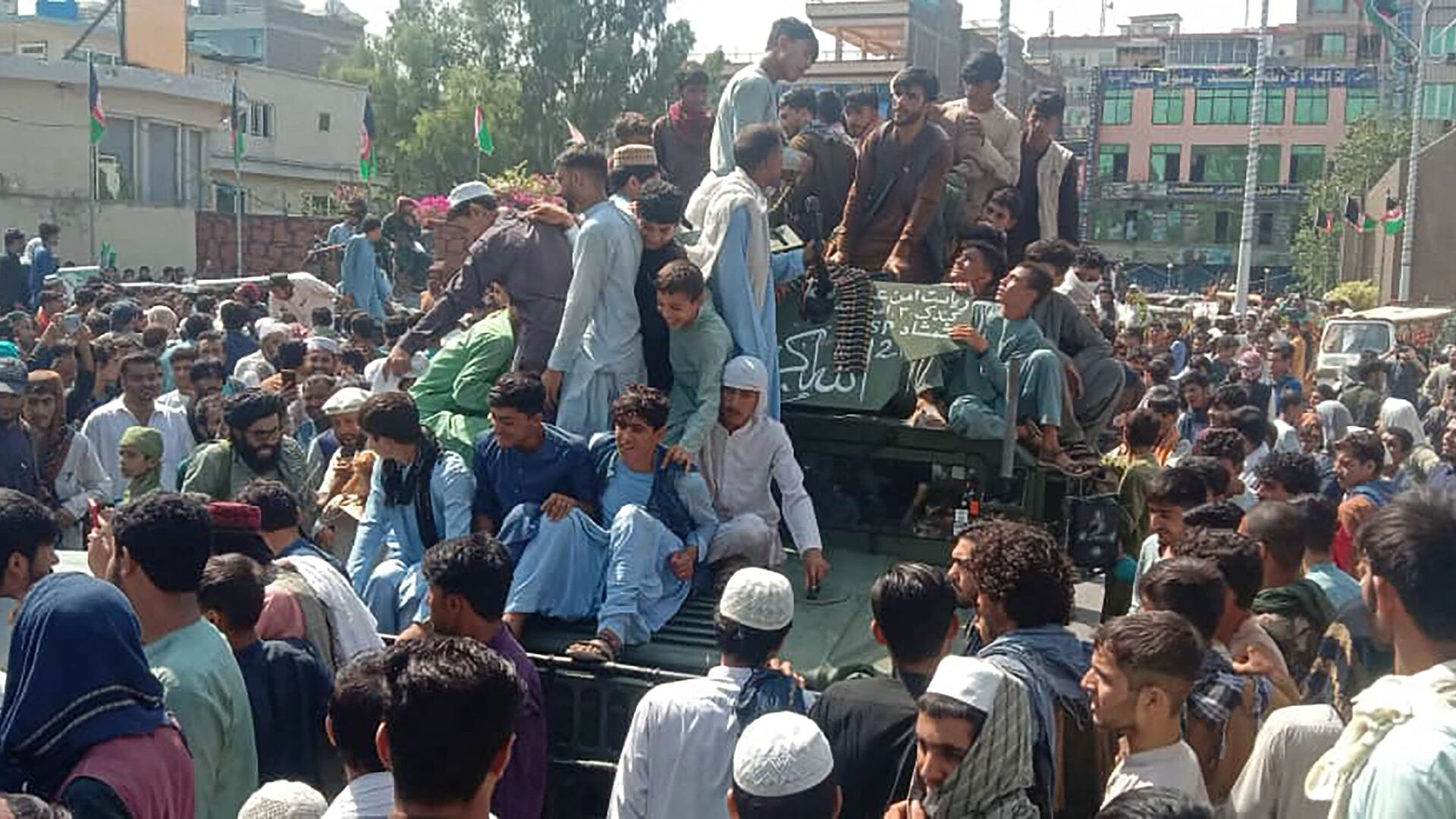 Bojownicy Talibana* i lokalni mieszkńcy siedzą w samochodzie Hammer Afgańskiej Armii Narodowej na ulicy w prowincji Dżalalabad 15 sierpnia 2021 roku. - Sputnik Polska, 1920, 16.08.2021