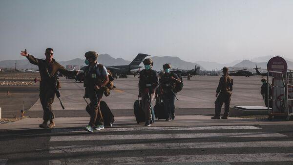 Морской пехотинец, прикомандированный к 24-му экспедиционному отряду морской пехоты, сопровождает персонал Государственного департамента для подготовки к эвакуации в международном аэропорту Хамида Карзая в Кабуле, Афганистан - Sputnik Polska