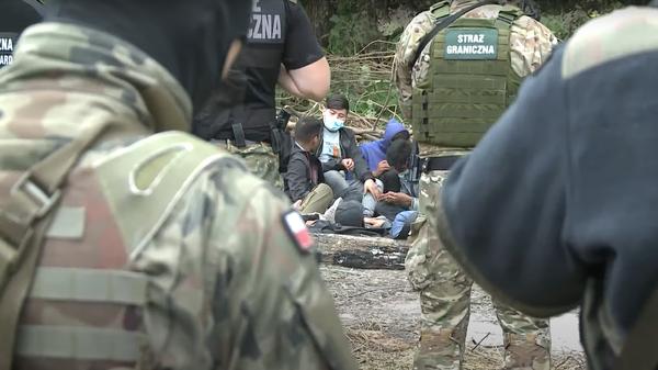 Мигранты в окружении солдат на границе Польши и Белоруссии - Sputnik Polska
