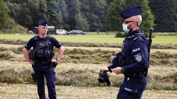 Польские полицейские и пограничники рядом с группой мигрантов, застрявших на границе между Белоруссией и Польшей - Sputnik Polska