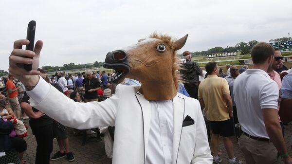 Мужчина в маске лошади делает селфи на скачках Belmont Stakes на ипподроме Белмонт-Парк в Нью-Йорке - Sputnik Polska