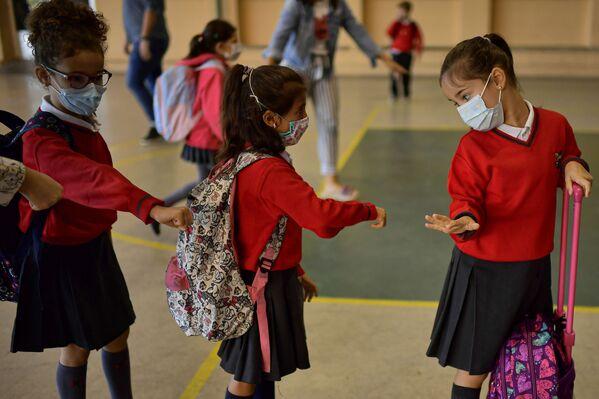 Grupa uczniów noszących maskę ochronną zapobiegającą rozprzestrzenianiu się koronawirusa czeka w kolejce przed wejściem do szkoły Luis Amigo w Pampelunie w północnej Hiszpanii  - Sputnik Polska