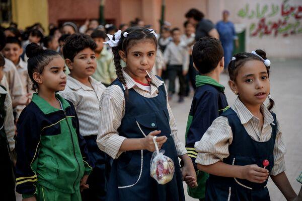 Uczniowie ustawiają się w kolejce na dziedzińcu szkoły Mahaba w Ezbet al-Nakhl, slumsach na północ od stolicy Egiptu, Kairu - Sputnik Polska