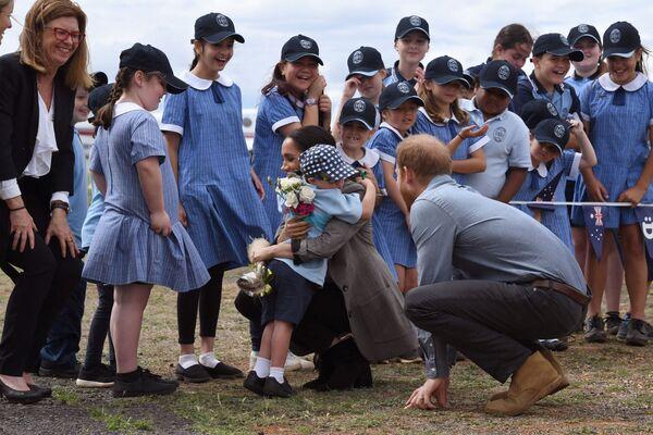 Brytyjski książę Harry patrzy, jak jego żona Meghan, księżna Sussex, jest przytulana przez studenta Luke'a Vincenta ze szkoły publicznej Buninyong po przybyciu pary na regionalne lotnisko Dubbo w Dubbo 17 października 2018 r.  - Sputnik Polska