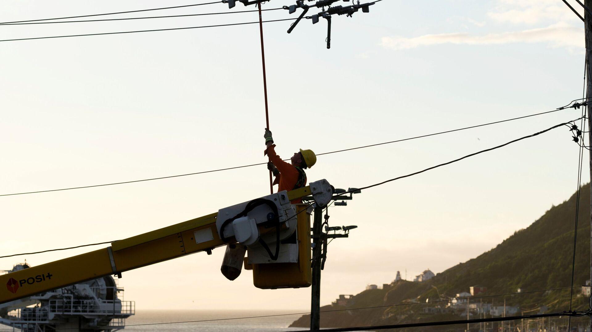 Pracownik firmy elektrycznej naprawia podarte linie energetyczne i słupy w porcie po huraganie Larry, który uderzył w St. Johns, Nowa Fundlandia, Kanada - Sputnik Polska, 1920, 11.09.2021