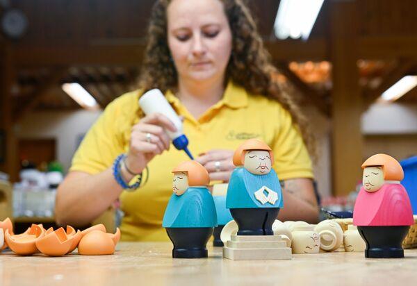Cena Clement, pracownik firmy Seiffener Volkskunst, robi miniatury niemieckiej kanclerz Angeli Merkel w Seifen w Niemczech - Sputnik Polska