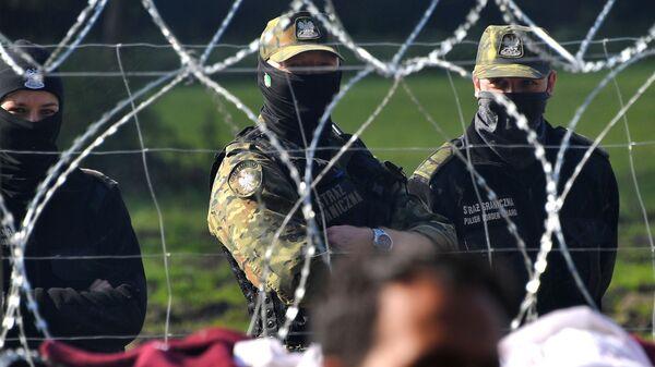 Польские пограничники наблюдают за лагерем беженцев из Афганистана на белорусско-польской границе возле деревни Уснар-Дольное - Sputnik Polska