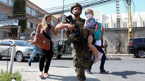 Военнослужащий несет школьника, когда мирные жители бегут из-за перестрелки в Бейруте, Ливан - Sputnik Polska