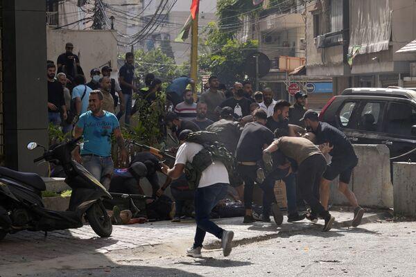 Zwolennicy ugrupowania szyickiego, które połączyło się z Hezbollahem, pomagają rannemu podczas starć zbrojnych na przedmieściach Bejrutu. - Sputnik Polska