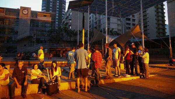 Ludzie ustawili się w kolejce po akumulatory z panelem słonecznym na placu w Caracas - Sputnik Polska