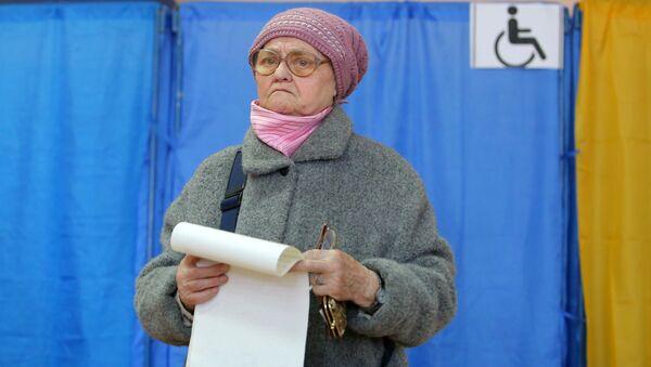 Mieszkanka Kijowa podczas głosowania na prezydenta Ukrainy w jednym z lokalów wyborczych  - Sputnik Polska