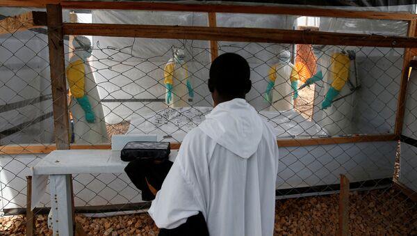 Duchowny obserwuje, jak pracownicy medyczni przygotowują ciało do pogrzebania w ośrodku leczenia Eboli w Butembo - Sputnik Polska