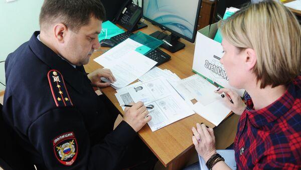 Funkcjonariusz policji i interesant w centrum wydawania rosyjskim paszportów mieszkańcom DRL i ŁRL w miejscowości Nowoszachtyńsk w obwodzie rostowskim - Sputnik Polska