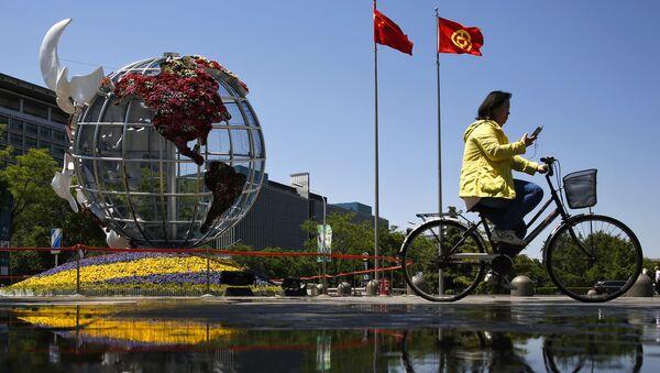 Kobieta na rowerze na placu przed bankiem w Pekinie - Sputnik Polska