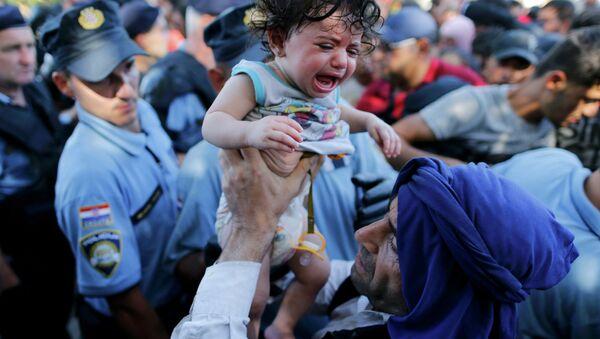 A migrant lifts a crying baby as he waits to board a bus in Tovarnik, Croatia, September 17, 2015 - Sputnik Polska