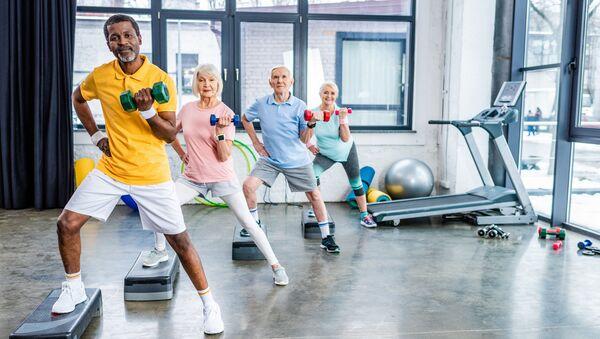 Пожилые люди тренируются в спортивном зале - Sputnik Polska