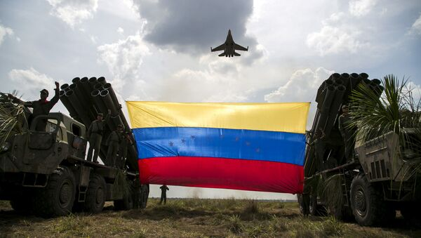 """Rosyjski myśliwiec Sukhoi Su-30MKV Sił Powietrznych Wenezueli leci nad flagą Wenezueli przywiązaną do wrzutni rakietowych w czasie ćwiczeń wojskowych """"Escudo Soberano 2015"""" - Sputnik Polska"""