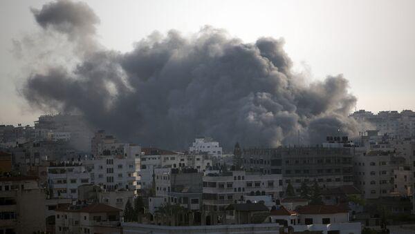 Czarny dym spowodowany przez izraelski nalot unosi się nad domami w mieście Gaza - Sputnik Polska