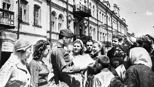 """Radziecki żołnierz pokazuje mieszkańcom wyzwolonego Mińska gazetę """"Prawda"""" - Sputnik Polska"""