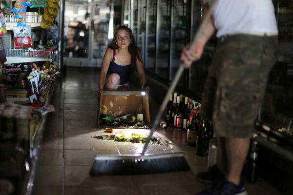 Kaitlin Alexander sprząta porozbijane butelki w supermarkecie - Sputnik Polska