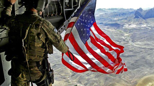 Amerykański żołnierz z flagą USA - Sputnik Polska